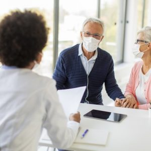 senior-couple-with-protective-facial-masks-receive-news-from-black-female-doctor-office_52137-35215